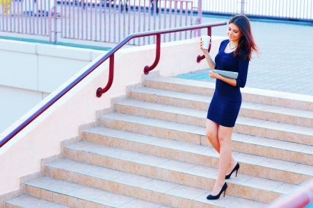 urban travel: Young beautiful businesswoman going down the stairs with coffee and tablet computer