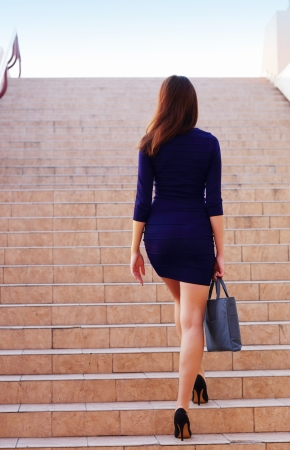 Businesswoman walking up the stairs photo
