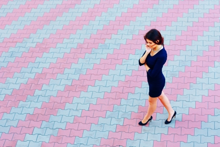 Young attractive businesswoman talking on phone while walking across the street photo