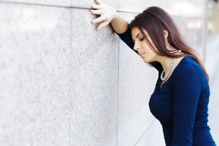 Portrait of tired businesswoman leaning at the wall photo