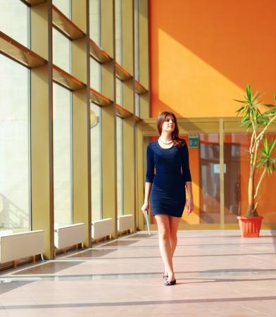 Businesswoman walking along the office corridor photo