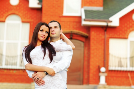 Happy couple standing in front of new home Stock Photo - 22572995