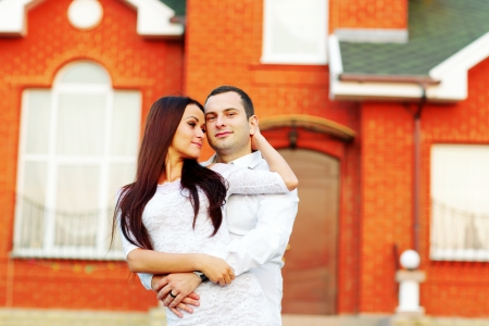 Happy couple standing in front of new home Stock Photo - 22614169