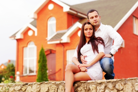 Happy couple sitting in the garden in front of new home Stock Photo - 22614171