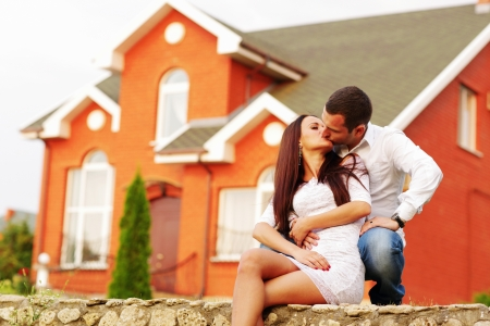 Happy couple kissing in front of new home Stock Photo - 22614172