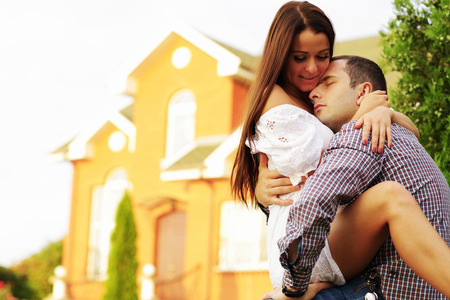 Happy couple sitting in the garden in front of new home Stock Photo - 22573003