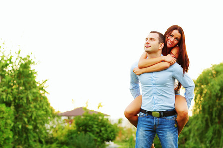 Happy woman jumped on man's back photo