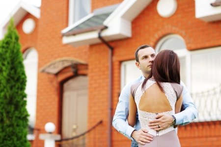 Happy couple standing in front of new home photo