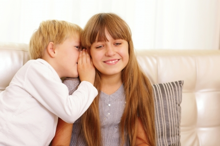 boy whispers something to his sister photo
