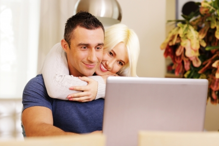 Happy beautiful couple with laptop at home Stock Photo - 23948582