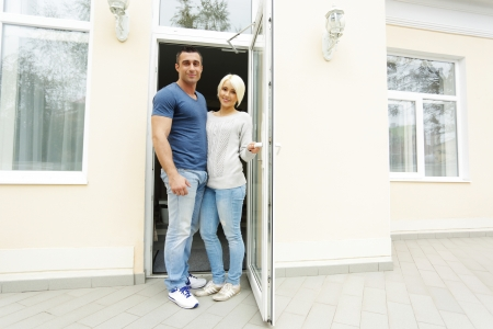 Happy couple welcomes you in their new house Stock Photo - 23948584