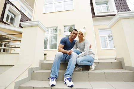 Happy couple sitting on the stairs in front of their house photo