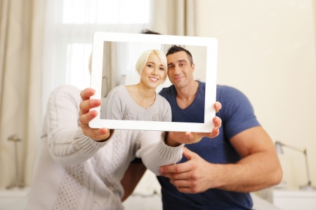 Happy couple taking a photo on the tablet PC Stock Photo - 23993428