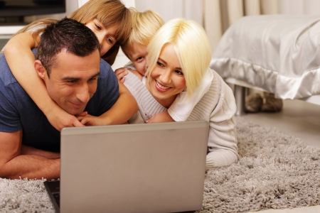 happy family lying on the carpet and playing on a laptop at home Stock Photo - 23993431
