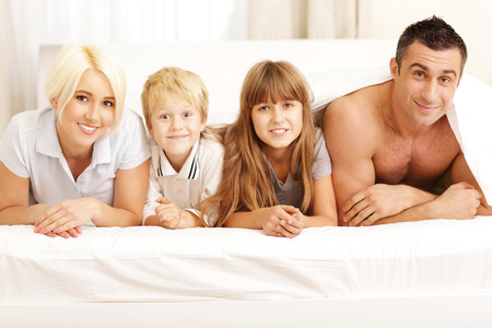 Happy young couple lying on the bed at home Stock Photo - 23993448