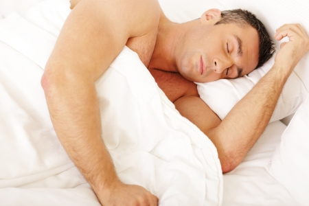 Young man sleeping on the bed at home photo