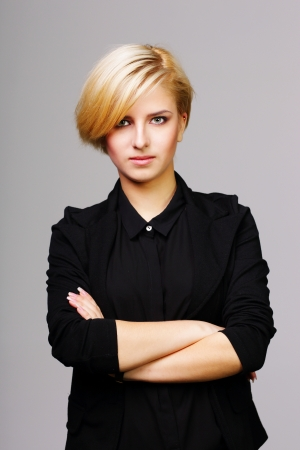 Confident beautiful young woman with arms folded on gray background photo