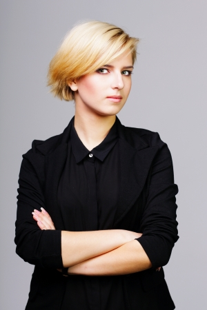 Confident young woman with arms folded on gray background photo