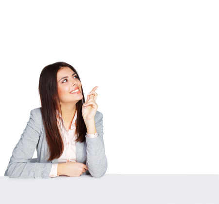 Young happy businesswoman sitting at the table and pointing up at copyspace photo