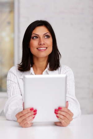 Happy beautiful businesswoman holding tablet computer and looking up photo