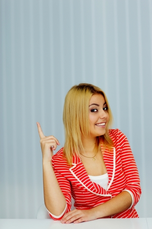 Happy young woman sitting at the table and pointing up at copyspace photo