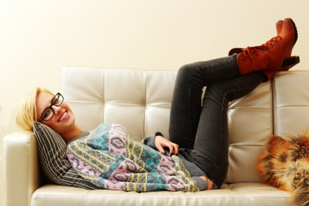 Young happy woman lying on the sofa at home photo