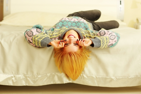 Young cheerful woman lying on the bed at home photo