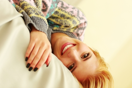 Closeup portrait of a young smiling woman lying on the bed photo