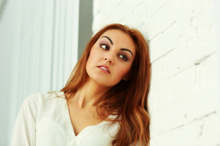 Pensive businesswoman leaning at the wall in office photo
