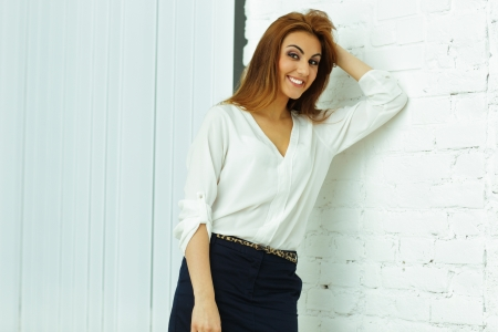 Cheerful businesswoman leaning at the wall in office photo