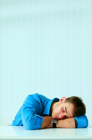 Young tired businessman sleeping at workplace in office photo