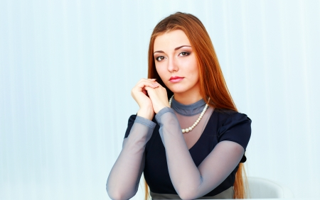 Young beautiful thoughtful woman sitting at the table isolated on a white background photo
