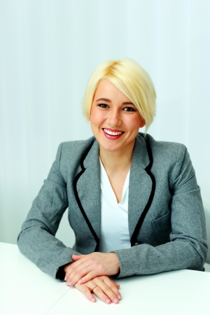 portrait of a young happy businesswoman sitting at the table in office photo