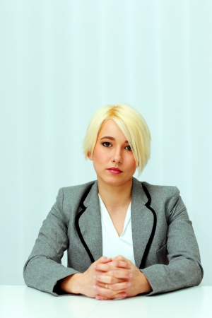 portrait of a young thoughtful businesswoman sitting at the table in office photo