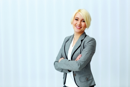 Young beautiful smiling businesswoman with arms folded in office photo