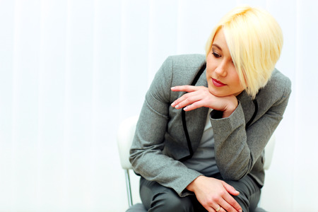 Young pensive businesswoman sitting at the chair and looking down isolated on a white  photo