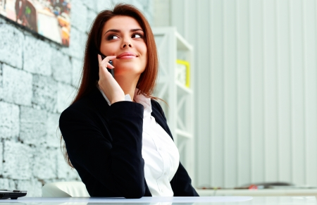 Young happy businesswoman talking on the phone and looking away at copyspace in office photo