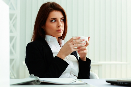 Young surprised businesswoman holding cup at office photo
