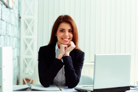 Young cheerful businesswoman sitting at the table on her workplace in office Stock Photo