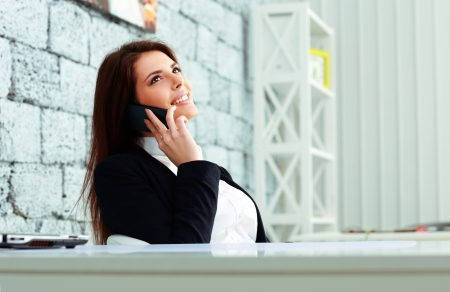 Young happy businesswoman talking on the phone and looking up at copyspace in office photo