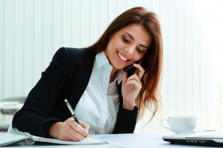 landline: Young happy businesswoman talking on the phone and writing notes in office Stock Photo