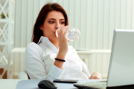 Young businesswoman drinks water on her workplace in office photo