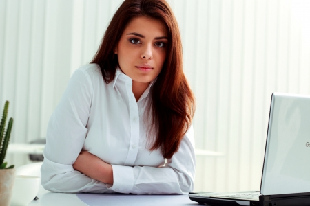 Young serious businesswoman sitting at the table in office photo