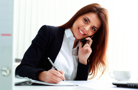 Young smiling businesswoman talking on the phone and writing notes in office photo