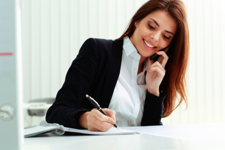 Young cheerful businesswoman talking on the phone and writing notes in office Stock Photo
