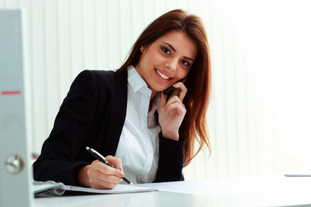 Young happy businesswoman talking on the phone and writing notes in office photo