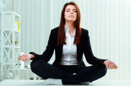 meditation woman: Young beautiful businesswoman meditates on the table in office