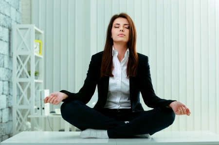 Young beautiful businesswoman meditates on the table in office photo