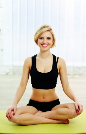 meditates: Portrait of a young fit woman sitting on the yoga mat and meditates