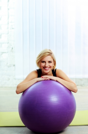 Young cheerful fit woman leaning on the fitball photo